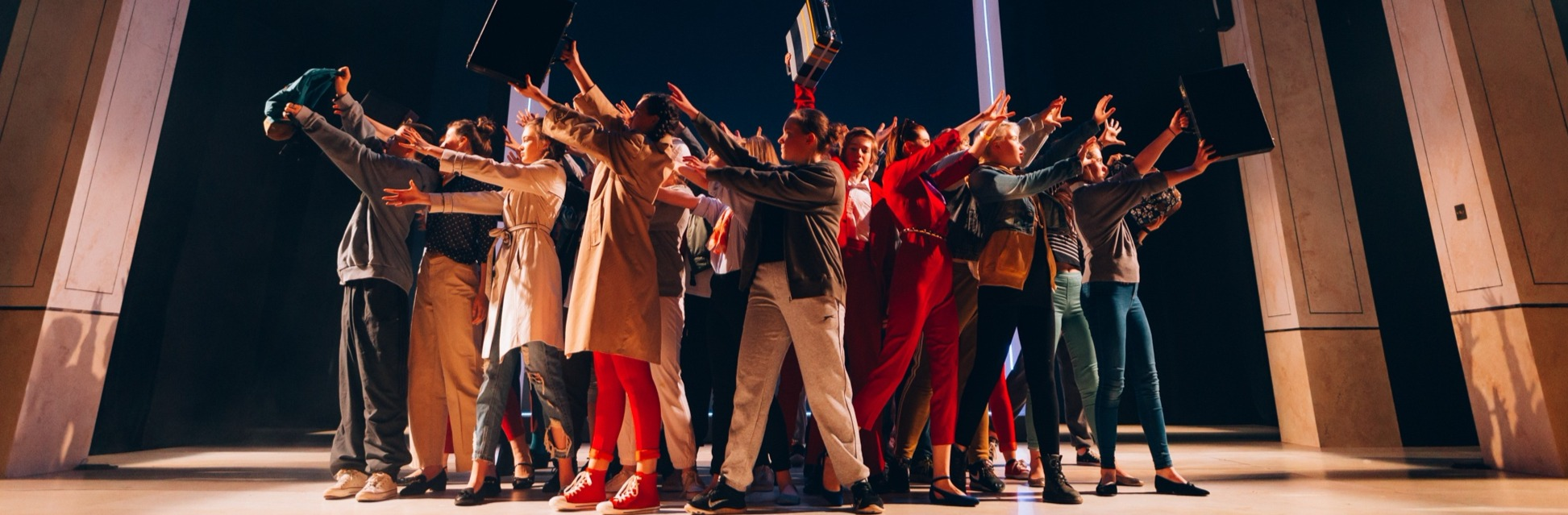 An image of the Youth Theatre production SUCCESS by Nick Drake showing the cast holding their arms upwards, some holding briefcases.