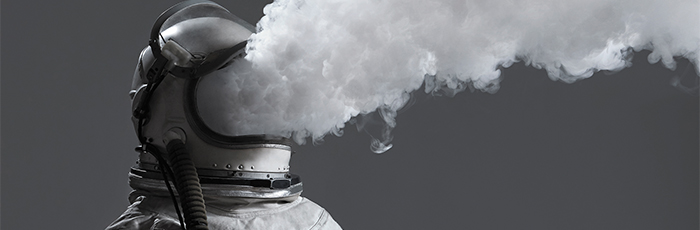 A photograph of an astronaut with their visor up and smoke pluming dramatically from where their face should be visible.