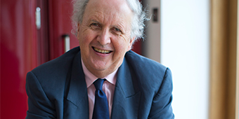 An image Alexander McCall Smith sitting with a cup of tea at a table and smiling