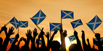 An image of many people holding up Scottish flags in the air