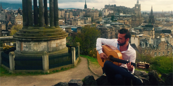 A picture of Daniel Martinez playing guitar at the top of Calton Hill in Edinburgh
