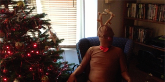 Daniel Kitson sits in an armchair next to a Christmas tree wearing a DIY Rudolf costume