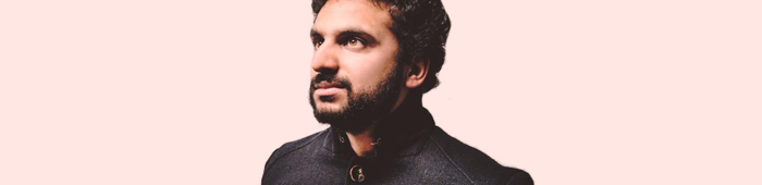 A portrait image of Nish Kumar against a plain light pink background